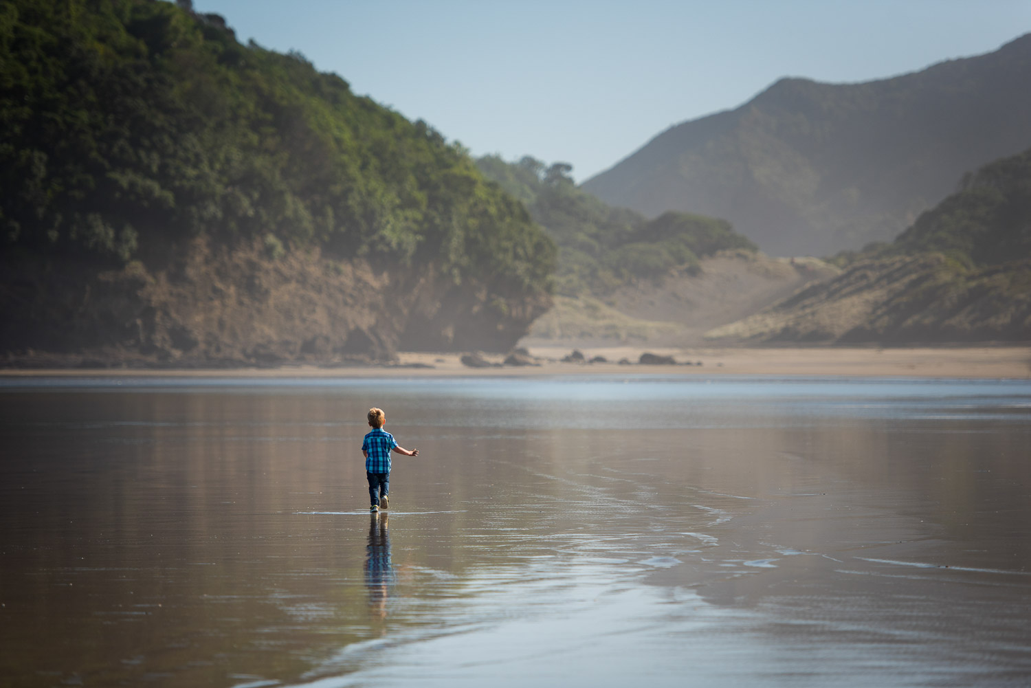 boy running at beach by auckland family photographer siobhan kelly photography