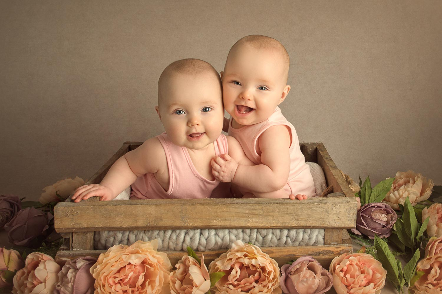 twin babies in a box with flowers