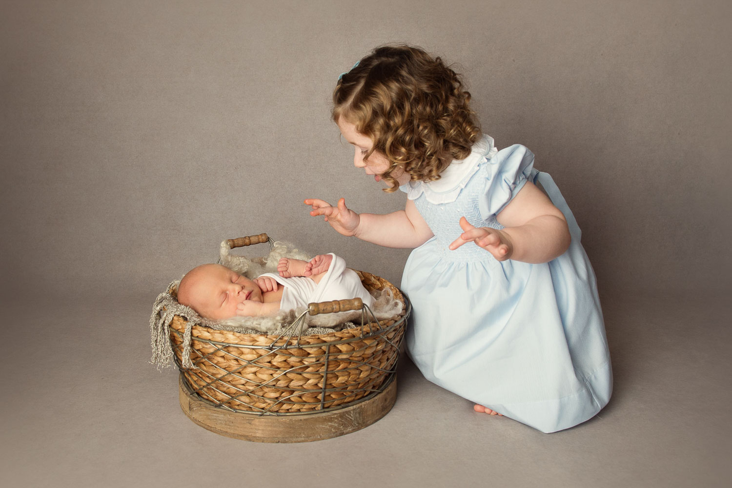 baby in basket with sister by siobhan kelly photography