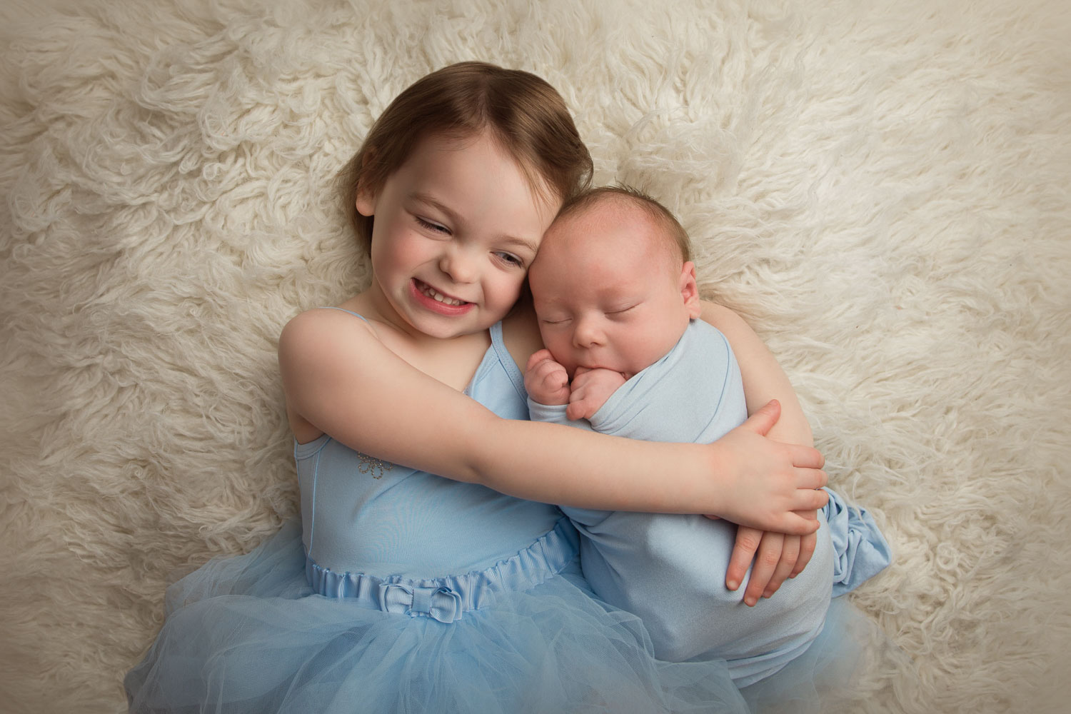Photograph of newborn baby and sister by auckland newborn photographer siobhan kelly photography